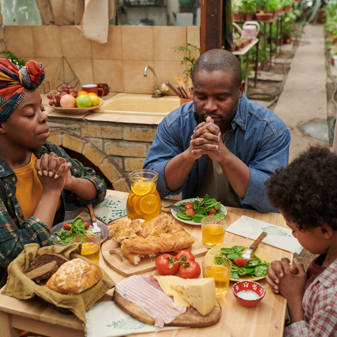 African family of three sitting at dining table and praying together before dinner